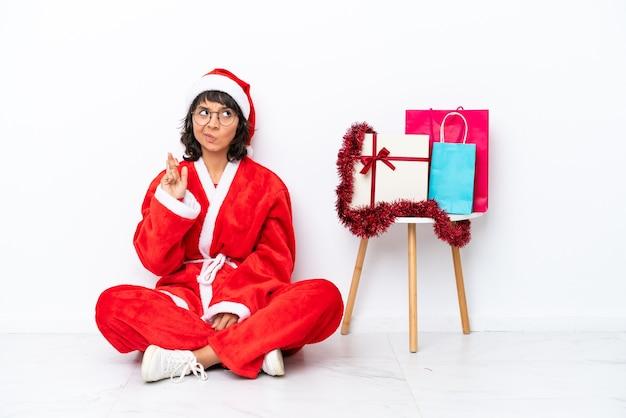 Giovane ragazza che celebra il natale seduta sul pavimento isolato su sfondo bianco con le dita incrociate e augurando il meglio