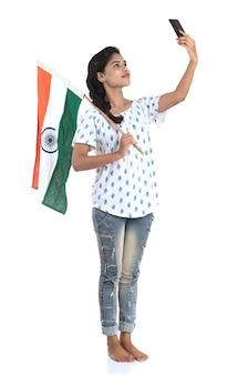 Ragazza che celebra il giorno dell'indipendenza indiana o il giorno della repubblica indiana utilizzando il cellulare con bandiera indiana o tricolore su bianco
