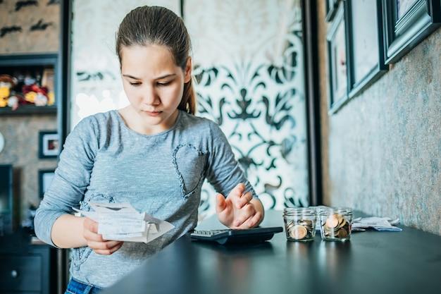 La ragazza controlla le bollette nella sua camera da letto. ci sono monete davanti a lei. messa a fuoco selettiva