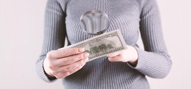 Una giovane ragazza controlla il dollaro con le lenti d'ingrandimento