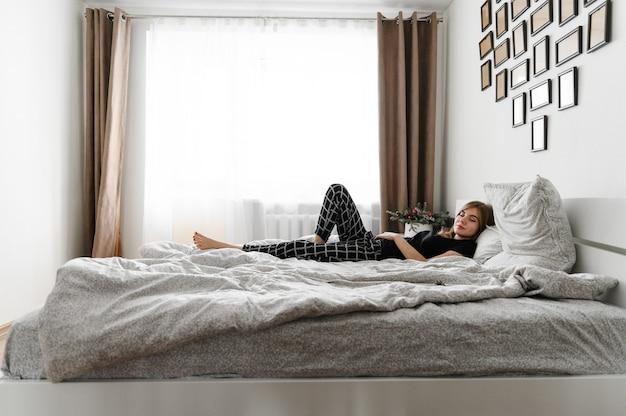 Giovane ragazza si trova allegramente a letto.