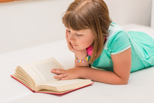 La bambina sta leggendo un libro sul divano di casa