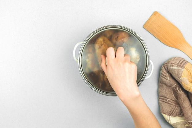 La ragazza ha cucinato la cena per suo marito, casseruola con pollo arrosto, cucchiaio di legno e asciugamano sul tavolo, sfondo minimalista, foto vista dall'alto