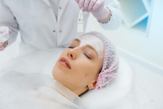 Una giovane ragazza in un ufficio di cosmetologia è sottoposta a procedure di ringiovanimento della pelle del viso. cosmetologia.