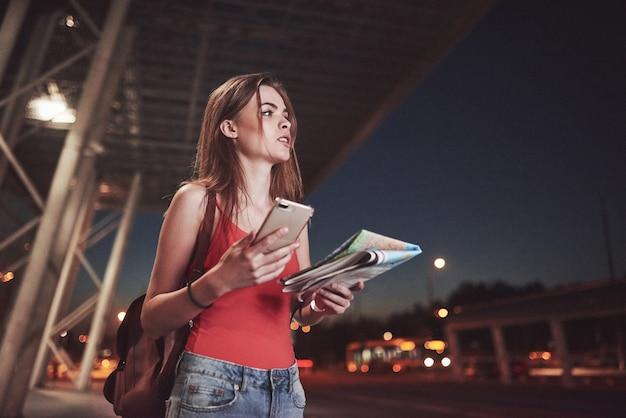 La ragazza costa di notte vicino al terminal dell'aeroporto o della stazione e legge la mappa della città