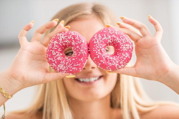 La ragazza si coprì il viso con ciambelle rosa nella cucina di casa. emozione mattutina a colazione.
