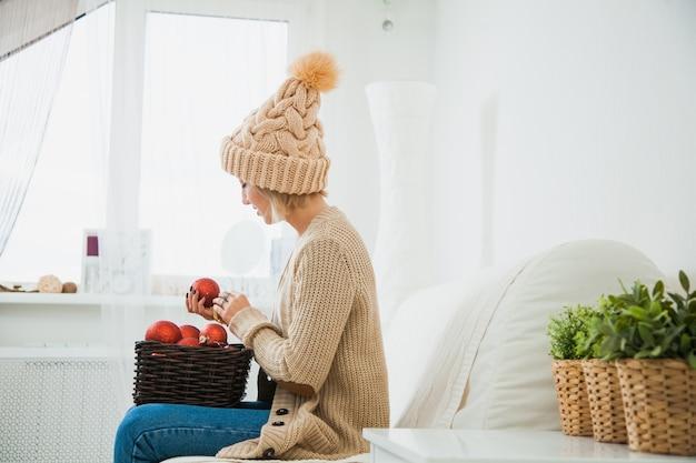 La ragazza in vestiti lavorati a maglia accoglienti tiene il cestino della decorazione delle palle di natale