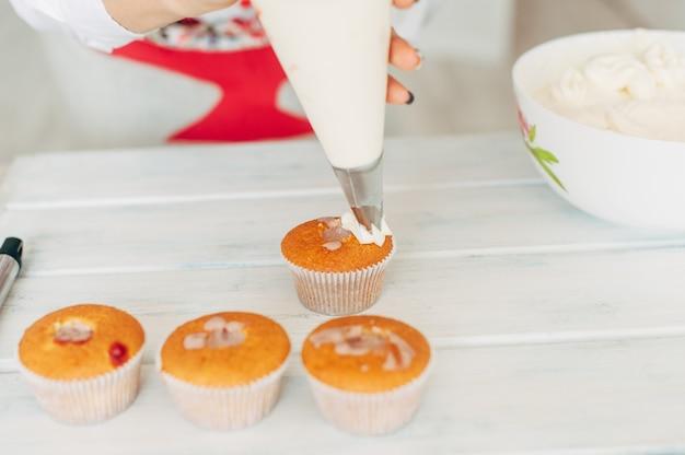 Una giovane ragazza decora i cupcakes con la crema.
