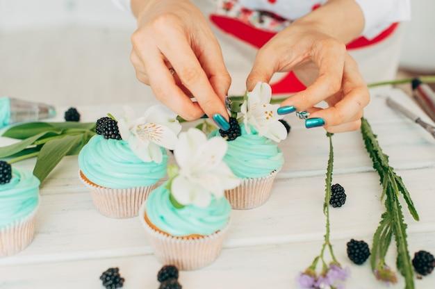 Una giovane ragazza decora cupcakes con fiori e bacche fresche