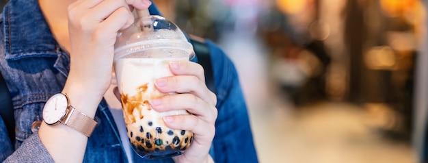 Giovane ragazza in giacca di jeans sta bevendo tè al latte con bolle di tapioca aromatizzato allo zucchero di canna con cannuccia di vetro nel mercato notturno di taiwan, primo piano, bokeh