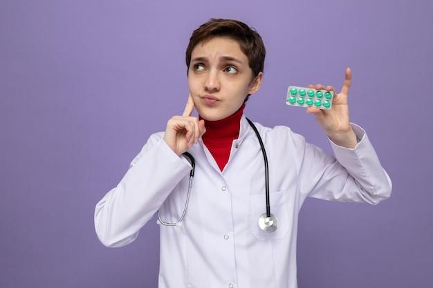 Medico della ragazza in camice bianco con lo stetoscopio intorno al collo che tiene la vescica con le pillole che osserva in su perplesso
