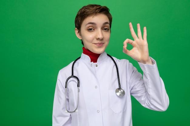 Medico della ragazza in camice bianco con lo stetoscopio felice e positivo sorridente fiducioso che fa segno giusto che sta sul verde