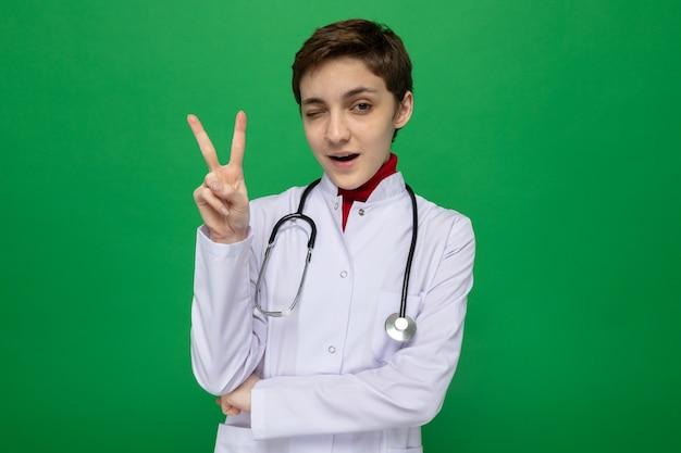 Medico della ragazza in camice bianco con lo stetoscopio che sorride ammiccante sicuro che mostra il v-segno che sta sul green