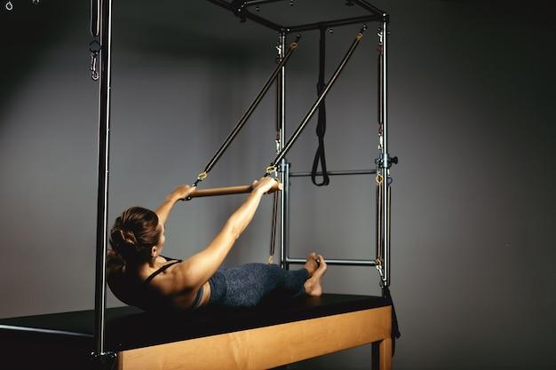 Una giovane ragazza fa esercizi di pilates con una macchina utensile a botte di riformatore del letto bella istruttore di fitness sottile sullo sfondo di un riformatore che fa vari esercizi arte di luce scura grigia