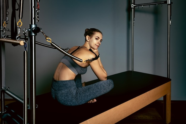 Una giovane ragazza fa esercizi di pilates con una macchina utensile a botte di riformatore del letto