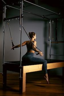 Una ragazza fa esercizi di pilates con un riformatore del letto