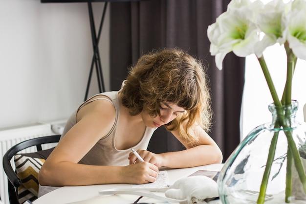 Ragazza che fa i compiti al tavolo bianco. educazione a casa e homeschooling