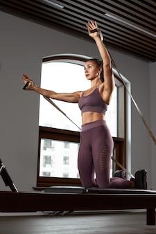 Ragazza giovane facendo esercizi di pilates con un letto riformatore. bellissimo istruttore di fitness sottile su sfondo grigio riformatore, chiave di basso, luce artistica. concetto di forma fisica.