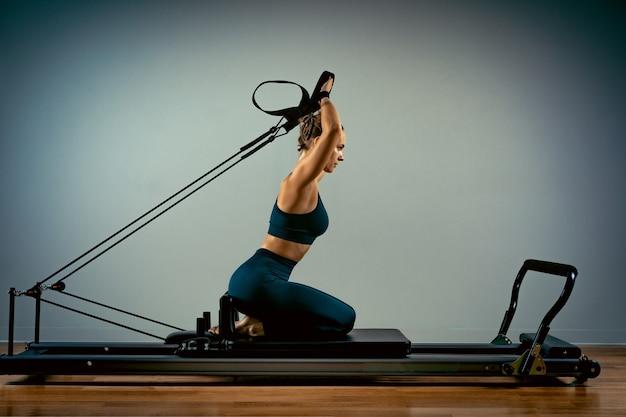 Ragazza che fa esercizi di pilates con un letto del riformatore