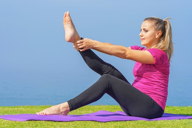 Ragazza che fa yoga che si siede su una stuoia di yoga sull'erba del mare di mattina. concetto di salute.