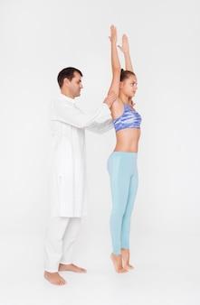 Ragazza che fa yoga con l'istruttore, classe di yoga accoppiata con l'allenatore.