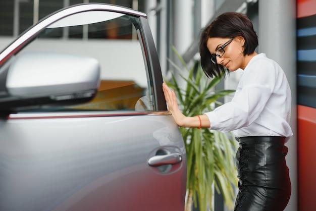 Giovane ragazza che sogna di una nuova auto ispezionando una nuova auto bianca presso una concessionaria di automobili, per un ulteriore acquisto a credito