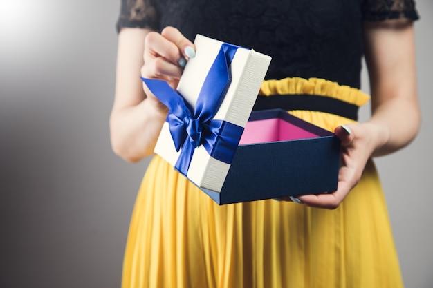 La ragazza in un vestito apre una confezione regalo su uno sfondo grigio