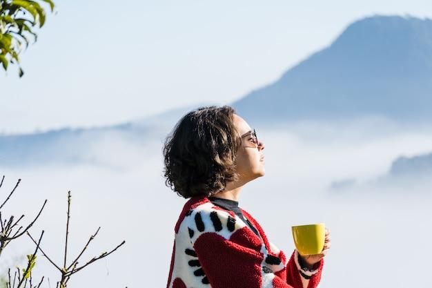 Giovane ragazza che beve caffè da una tazza in una giornata fredda troppa nebbia e nuvole coprono la vista della città