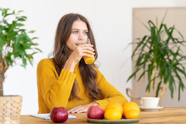 Giovane ragazza che beve succo d'arancia, sorridente. bella donna con i capelli lunghi