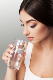 La ragazza beve l'acqua. aspetto sano del viso. ritratto di una ragazza. il concetto di bellezza e salute. su uno sfondo grigio.