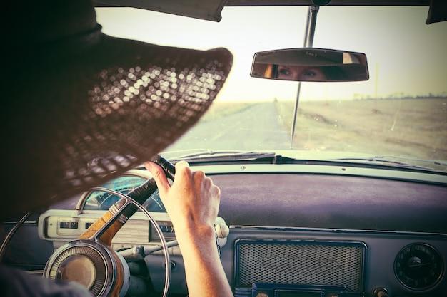 Giovane ragazza alla guida di un'auto retrò lungo la strada nei campi