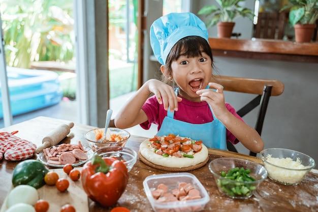 Ragazza che mangia pizza sul tavolo in cucina