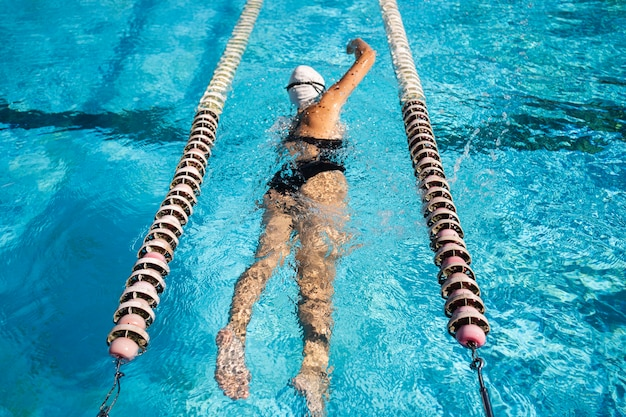Ragazza giovane godendo di nuotare in piscina