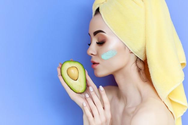La ragazza gode della maschera facciale crema con l'asciugamano giallo sulla testa.