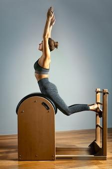Giovane ragazza esercita su un letto di riformatori di pilates