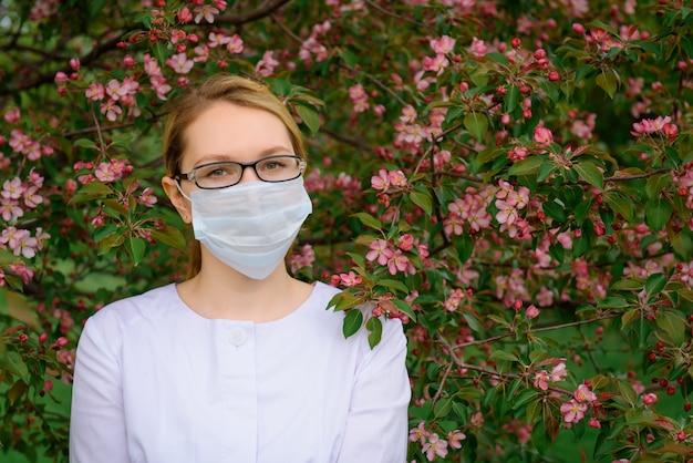 Ragazza in occhiali e mascherina medica dall'albero di fioritura. ritratto di bello medico femminile ben curato nel parco di verde di estate.