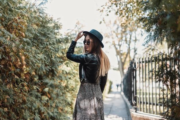 Una giovane ragazza in abiti alla moda con un cappello cammina per strada in una giornata autunnale