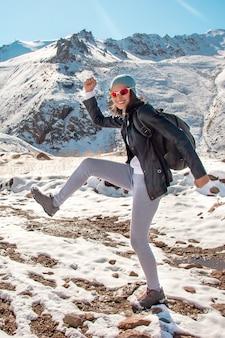 Una giovane ragazza con gli occhiali balla sulla neve. montagne in inverno.