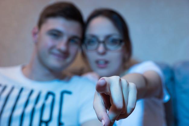 La giovane ragazza con gli occhiali sta puntando verso la messa a fuoco della fotocamera sul suo dito seduto su un divano con il suo ragazzo a casa a guardare la televisione, vista frontale nel bagliore blu dal set