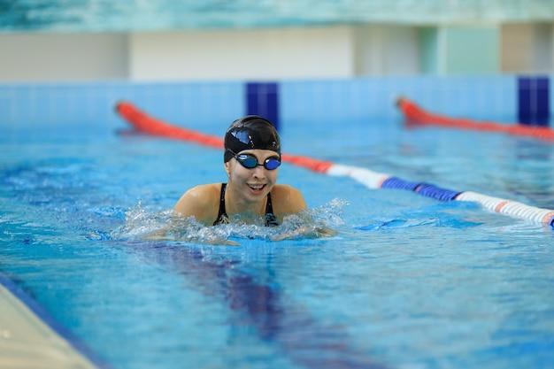 Giovane ragazza in occhiali e berretto da nuoto in stile colpo di farfalla nella piscina di acqua blu.