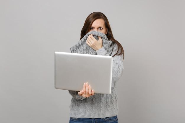 La giovane ragazza in maglione grigio che copre il naso della bocca con la sciarpa lavora al computer del pc portatile isolato su fondo grigio. trattamento online di stile di vita sano che consulta il concetto di stagione fredda. mock up copia spazio.