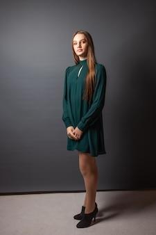 Una giovane ragazza in un abito verde rigoroso posa in uno studio fotografico su uno sfondo grigio