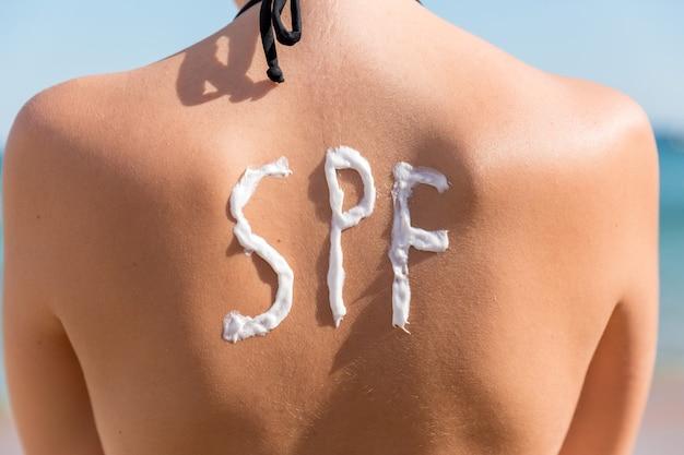 La ragazza ha una parola spf sulla schiena fatta di crema solare in spiaggia. concetto di fattore di protezione solare.
