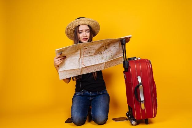 Una giovane ragazza con un cappello viaggia con una grande valigia rossa, studia una mappa della città