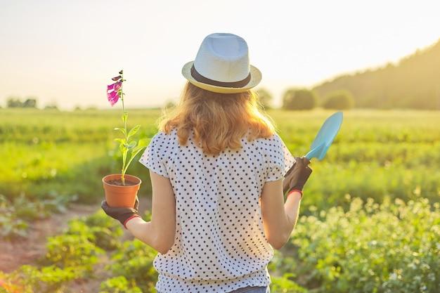 Giovane ragazza in cappello con guanti passeggiate in giardino con pala e fiore pianta in vaso