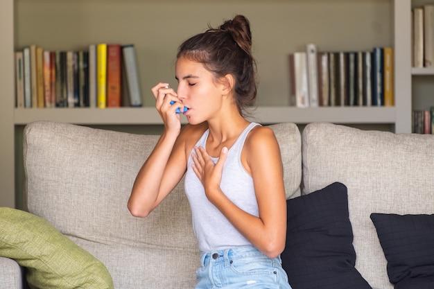 Ragazza che ha un attacco d'asma e utilizzando un inalatore seduto su un divano a casa