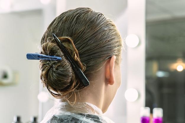 Ragazza che ha maschera di trattamento dei capelli in un salone di bellezza, ragazza durante il processo di cura