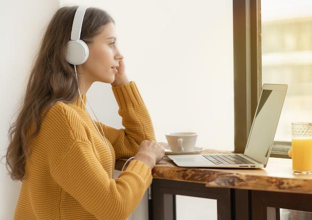 Giovane ragazza in cuffie studiando online, utilizzando laptop e facendo colazione