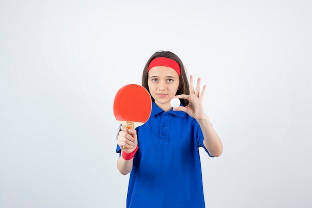 Una giovane ragazza con palla con racchetta da ping pong