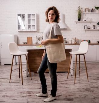 Ragazza che tiene una borsa di stoffa. in cucina. non sono di plastica.